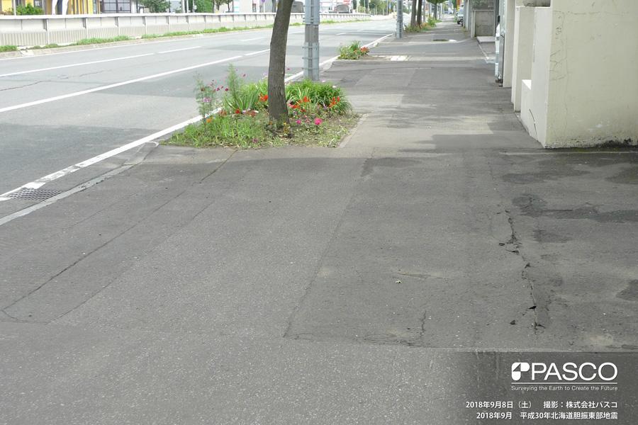 札幌市清田区清田三条1丁目付近 歩道のアスファルトに圧縮変形が生じている。旧版地形図による谷地形に直交する方向に発生していることから、地盤が道路中心方向(写真左方向)の谷の下方に向かって移動したと推定される。
