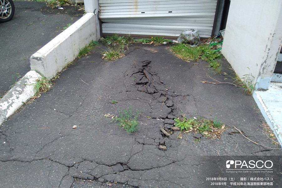 札幌市清田区里塚一条1丁目~2丁目付近 アスファルトに圧縮変形が生じシャッターが変形している。旧版地形図の谷部に位置している。