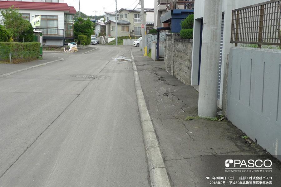 札幌市清田区里塚二条2丁目付近 アスファルトに圧縮変形が発生。旧版地形図の谷方向に直交しており、地盤が谷方向に流動したことを示唆。