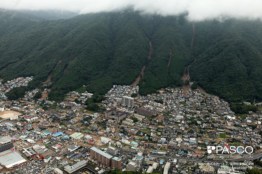 広島県広島市安佐南区八木町 複数の谷で土石流が発生し、土砂が市街地に氾濫堆積している。土石流が発生した渓流では沢沿いに流水が確認できる。