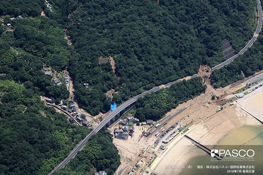 広島県安芸郡坂町水尻 広島呉道路で発生した斜面崩壊。手前はJR呉線水尻駅、国道31号に流入した土砂