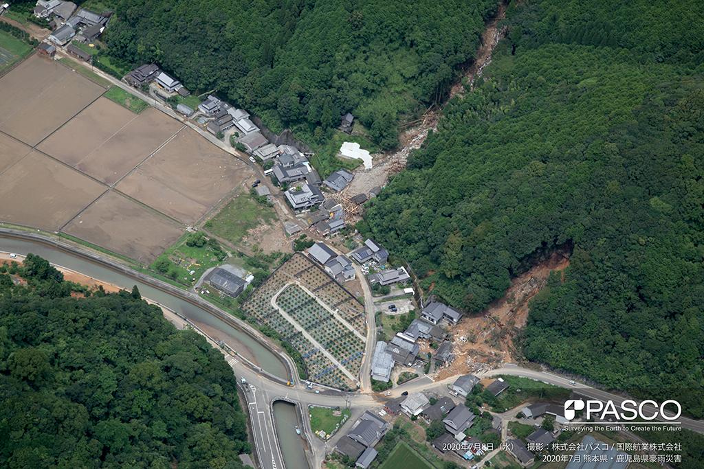 熊本県葦北郡芦北町大字女島付近:土石流が発生し、土砂が住宅地に流入している。住宅地に流木が堆積している様子が確認できる。