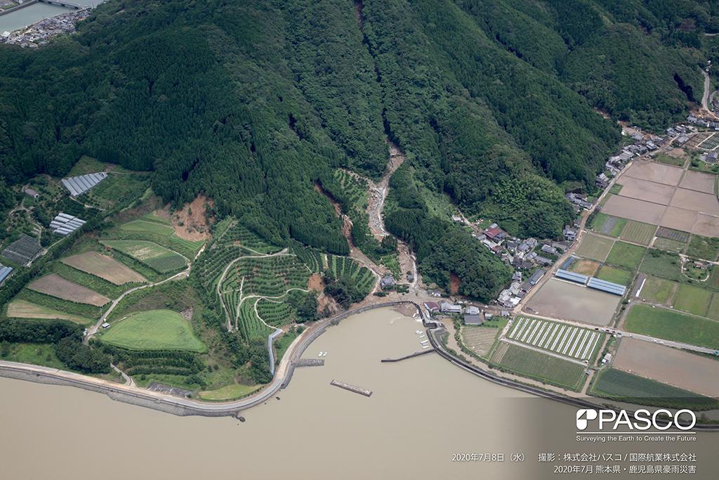熊本県葦北郡芦北町大字女島付近:流域内の堰堤の左袖部を乗り越えて土石流が流下している様子が確認できる。
