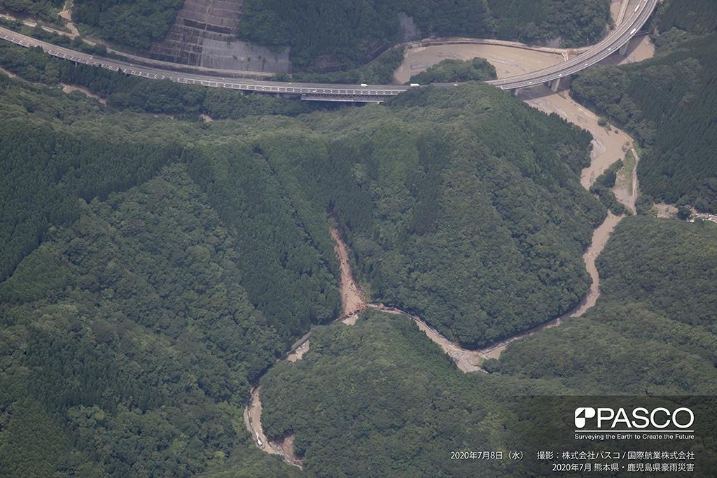 球磨郡山江村大字万江宇那川左岸側:斜面崩壊により土砂が宇那川へ流出し、流木の一部が道路に堆積している。下流側では宇那川が閉塞している様子も確認できる。
