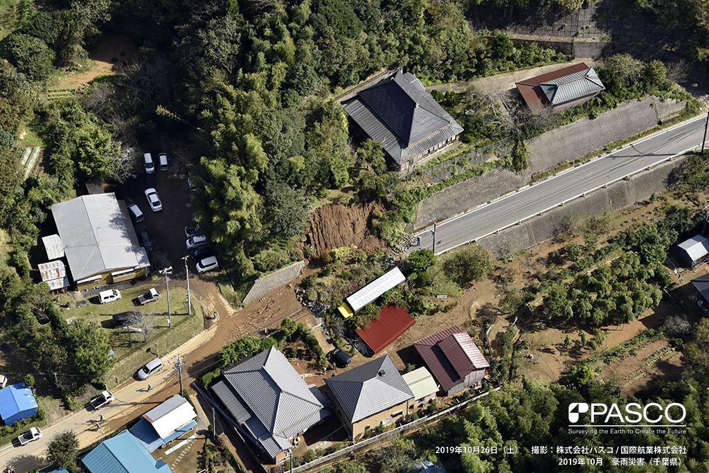 長柄町長柄山付近で発生した斜面崩壊: ブロック積擁壁を破壊して、斜面下の道路、住宅に崩壊土砂が堆積している。トラックが崩壊土砂上に乗り上げている。
