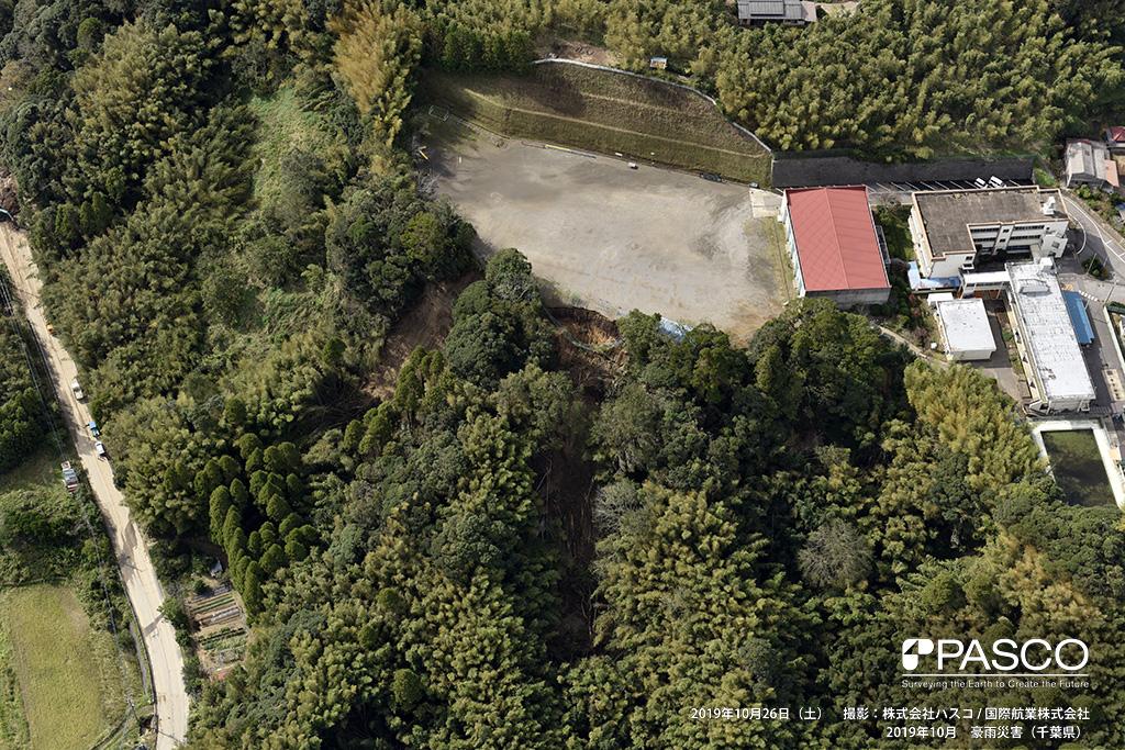 長柄町山根付近: 長柄小学校のグランド法肩に斜面崩壊が見られ、フェンスが崩れている。