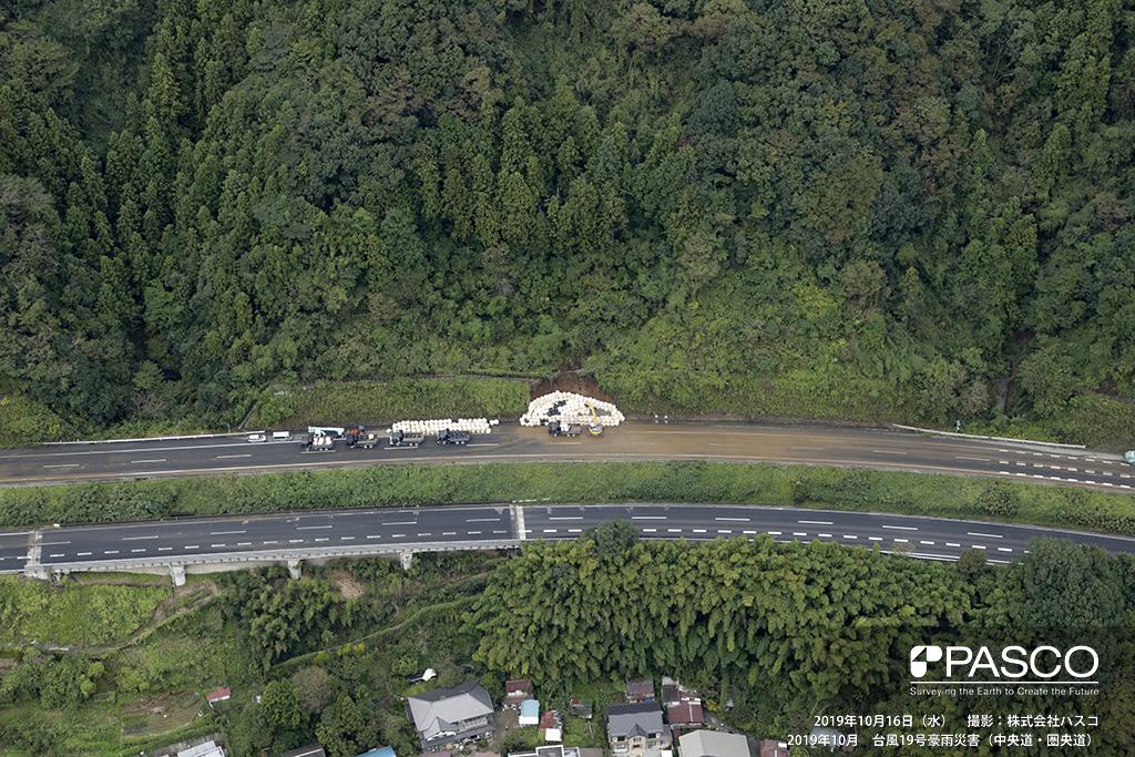 中央道・圏央道: 中央道 小仏トンネルより東京側、約900m付近の道路被災箇所。 道路上部の斜面が崩壊し、高速道路上に土砂が堆積している。