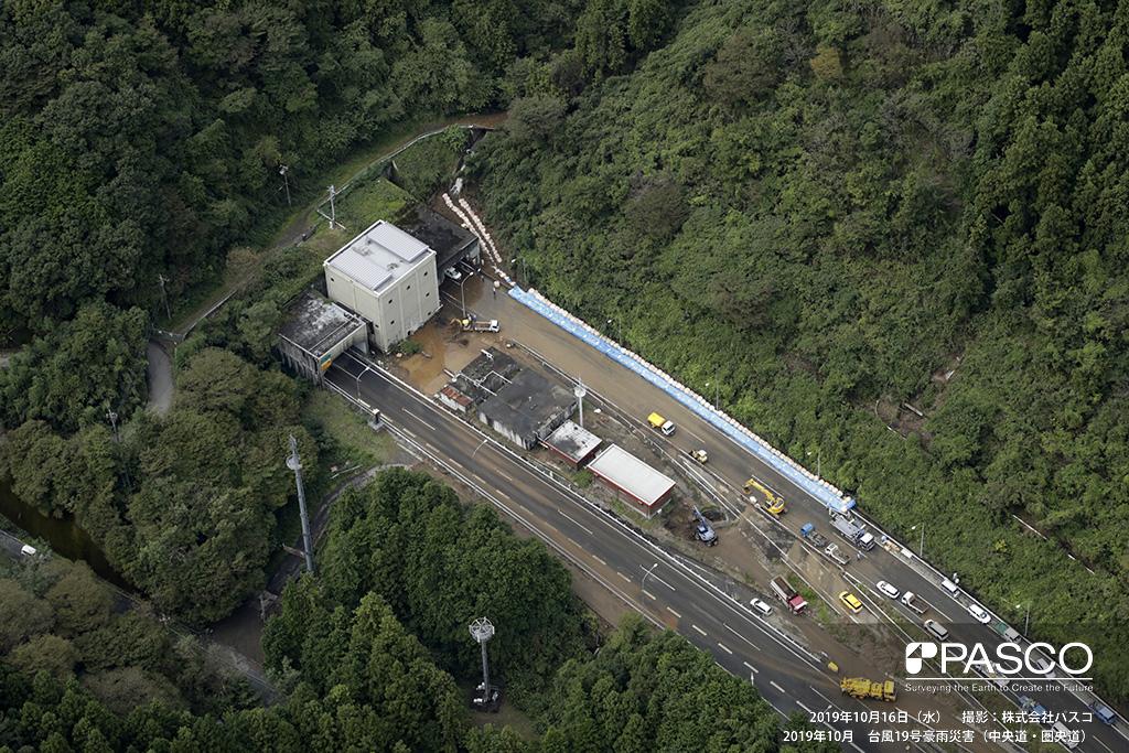 中央道・圏央道: 中央道 小仏トンネル東京側入り口付近の道路被災箇所。 北側(写真上方)にある沢から流出した水や土砂が高速道路上を覆っている。