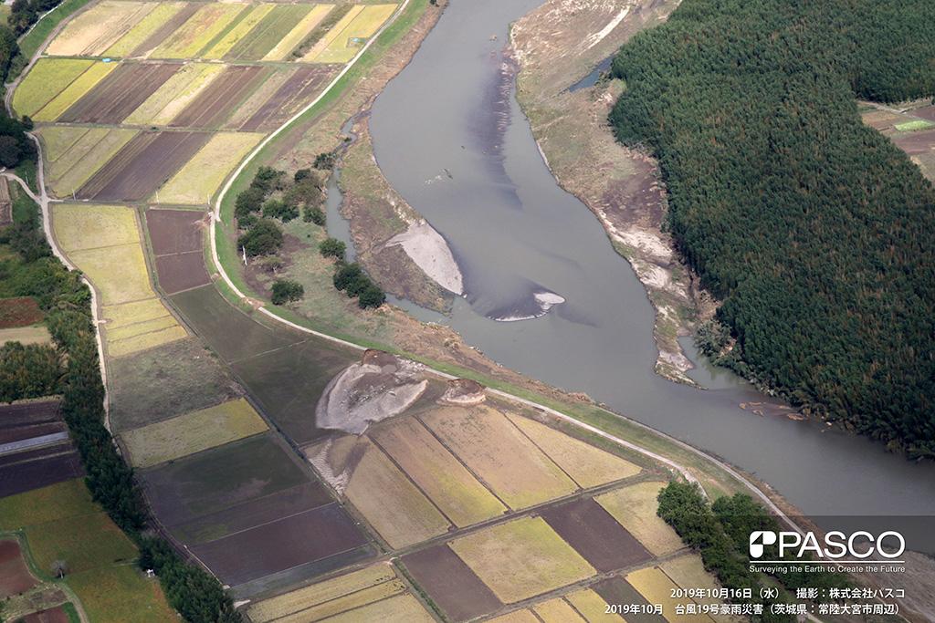 茨城県常陸大宮市 久慈川破堤箇所(下流側から上流を望む): 右岸側水衝部(2箇所)で堤防の決壊している。他にも越流したと思われる箇所が数ヵ所確認できる。